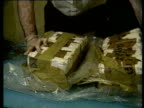 EXT MS man counting money following drug deal / INT CMS police officer's hands pulling apart large consignment of seized drugs / haul of seized drugs...