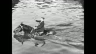 Buster Keaton crosses a river on a horse and uses oars as if he is rowing a boat