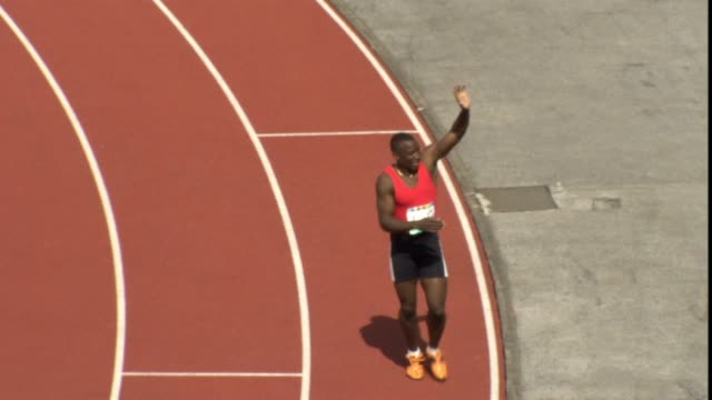 HA WS PAN Man crossing finish line during race and waving to the crowd/ Other running hugging winning/ Man waving to crowd/ Sheffield, England