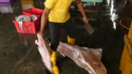 Man cutting off bow ray fins for sale in shark fin soup