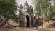 WS A man cycles through Angkor Thom North Gate in Angkor Wat / Siem Reap, Cambodia