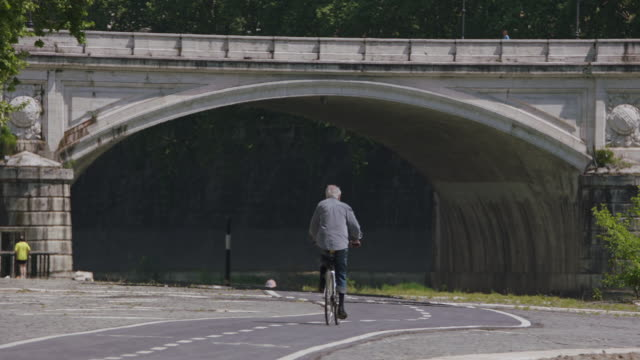 WS Man cycling near arch bridge / Rome, Italy