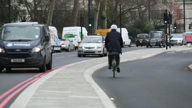 WS Man cycling on bicycle lane in Victoria Embankment / London, England, United Kingdom