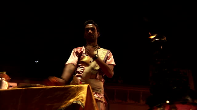A man dances in front of an altar.
