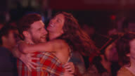 Man dances with girlfriend, picks her up, and spins her around in crowd at outdoor music festival