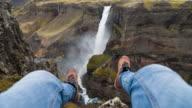 Man met zijn voeten, zittend op de rand van een ravijn bungelen