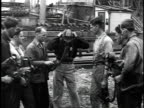 1929 MONTAGE Man demonstrating putting on a gas mask to workers / United States