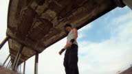 A man does a parkour freerunning backflip under a pier on the beach. - Slow Motion - Model Released - HD