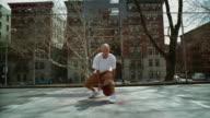 WS Man doing dribbling tricks with basketball on Morningside Park basketball court/ Harlem, New York