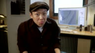 MS, Man doing faces sitting in office, Brooklyn, New York City, New York State, USA
