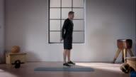 Mann bei seinem Training im Fitnessraum (Kniebeugen
