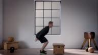 Mann bei seinem Training im Fitnessraum (Kniebeuge geradeaus weiter