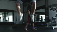 man doing jump squats while his trainer motivates him