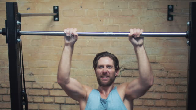 Man doing pull-ups in gym