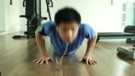 Man doing push ups exercises at fitness gym with a smartphone