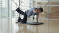 WS DS Man doing stretching exercising over mat floor in gym / Vancouver, British Columbia, Canada
