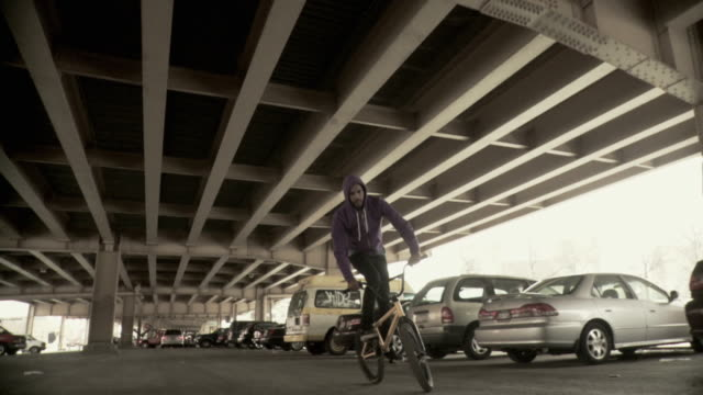 MS LA DS SLO MO Man doing tricks on BMX bicycle under overpass, Brooklyn, New York City, New York State, USA