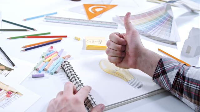 Man drawing light bulb and doing thumb up after finishing