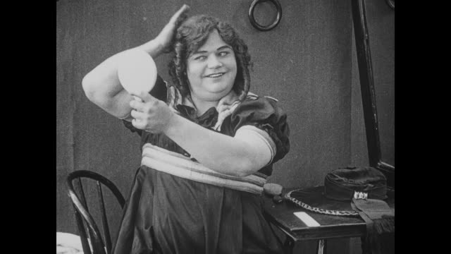 Fatty Arbuckle, dressed as woman, preens in front of bathhouse mirror before skipping away with parasol