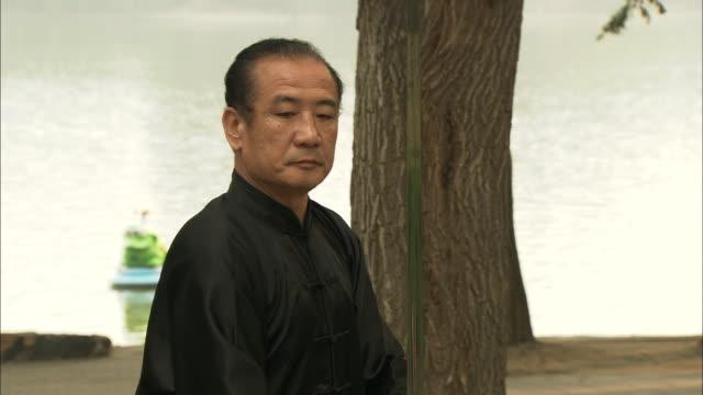 MS ZI CU Man dressed in black performing sword dance in Yuyuantan park, Beijing, China