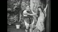 Buster Keaton, dressed in drag, and Fatty Arbuckle, wearing a leopard skin, dance for the large audience, and when Keaton jumps into Arbuckle's arms, they receive great applause from everyone except for one jeering man