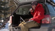 Man drinking coffee and working on laptop while sitting in back of car / Ketchum, Idaho, United States