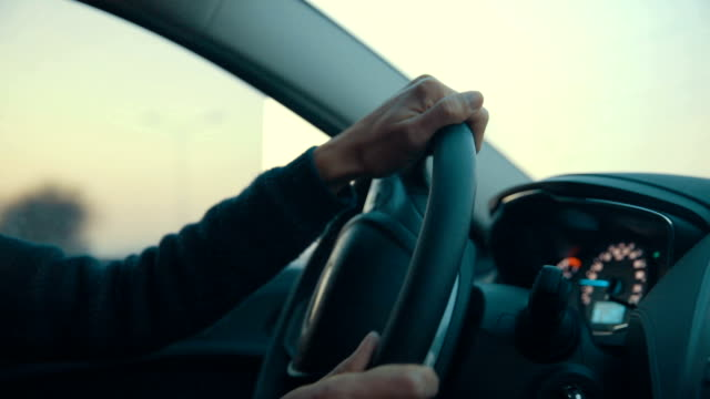Man driving car, holding steering wheel