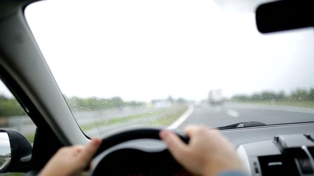 Menschen fahren Auto an regnerischen Tag