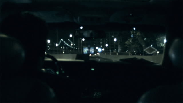 ms pov man driving car through city street at night new