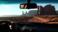 POV Man driving car through Monument Valley, view of Three Sisters, Arizona, USA