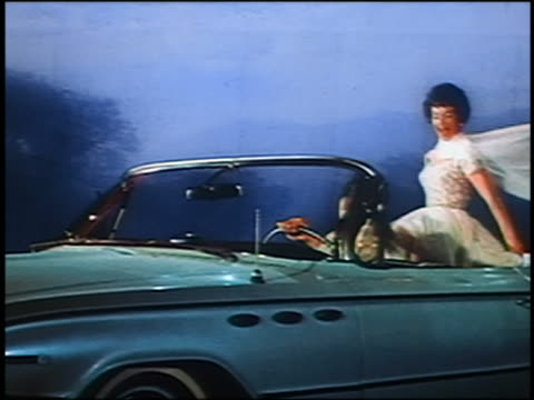 1961 man driving convertible Buick with female model sitting in back spinning / projected scene in background