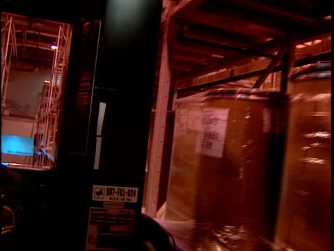 MS TS Man driving forklift near shelves in distribution warehouse / New Jersey, USA