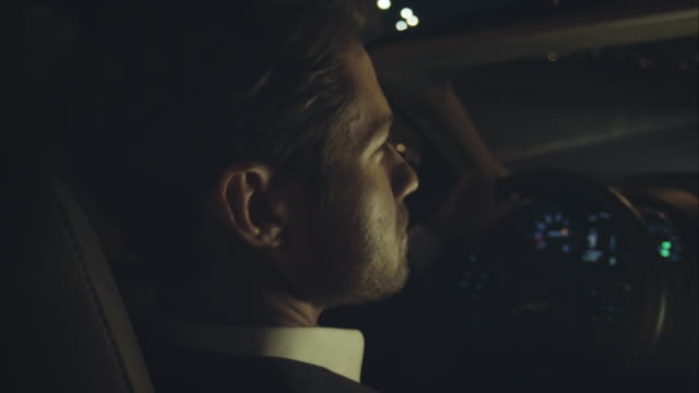 Man driving luxury car at night