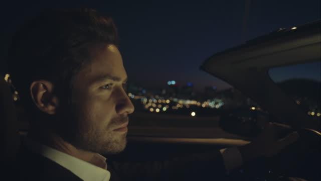Uomo guida auto di lusso a notte