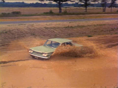 1960 PAN man driving thru mud puddle on dirt road next to paved road / industrial