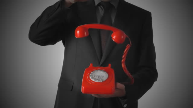 Man dropping down red phone receiver on dial phone