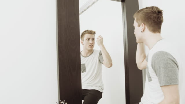 Man drying eyebrows in front of a mirror