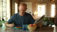 MS, Man eating breakfast and reading newspaper in cottage, North Truro, Massachusetts, USA
