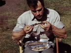 1949 MS Man eating plate of fresh caught fish during camping trip / USA