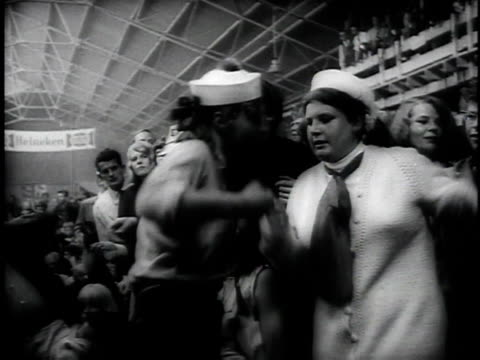 man eating sandwich / crowd dancing / women fainting and being pulled out of crowd