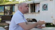 Man Eating Tortilla Wrap At Food Trailer Park