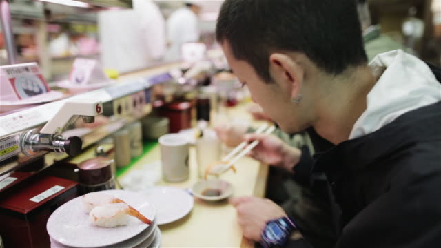 CU A man eats in a sushi-go-round restaurant / Tokyo, Japan