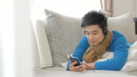 Man Enjoy Listening to Music and touching smartphone in relax time at home , Lifestyle and Relaxation concept