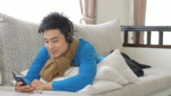 Man Enjoy Listening to Music and touching smartphone in relax time at home , Lifestyle and Relaxation concept , Panning right to left movement