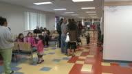 Man entering job center office ZI ZO children playing TU People waiting in line/ Antioch California USA/ AUDIO