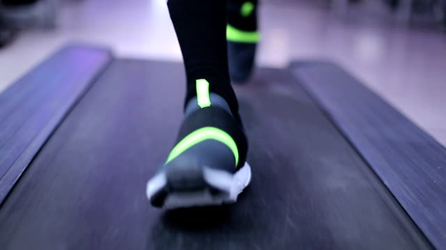 Mann Training auf dem Laufband im Fitnessraum