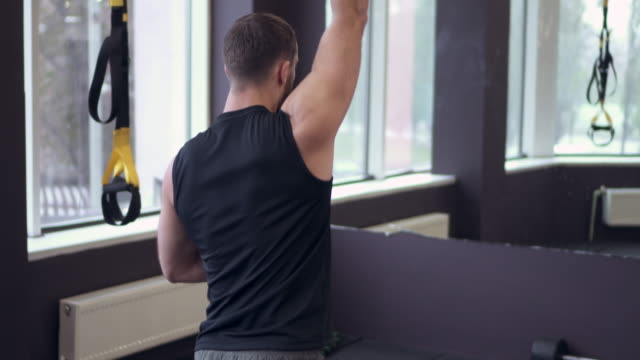 Man exercising with dumbbell on fitbal