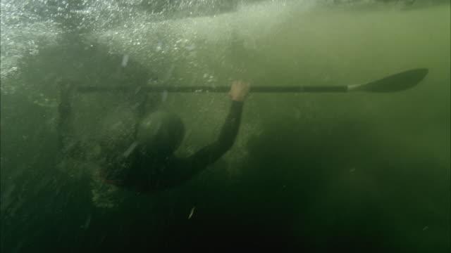 SLO MO WS Man falling off paddle board into water / Aspen, Colorado, USA