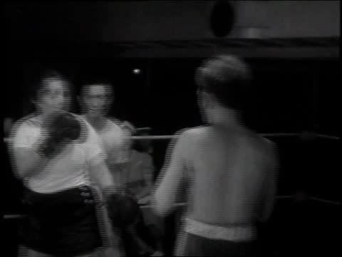 1939 MONTAGE Man fighting woman in a boxing match / New York City, New York
