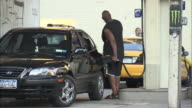 WS, Man filling car at Manhattan gas station, rear view, New York City, New York, USA